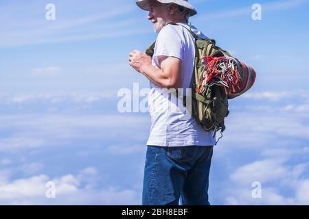 Portrait de voyageur d'un vieil homme Profitez de la vue sur les nuages sur le dessus - sac à dos et couverture de style rétro colorée sur le dos. Un style de vie heureux et des personnes modernes - homme senior et mûr dans les activités de loisirs en plein air Banque D'Images