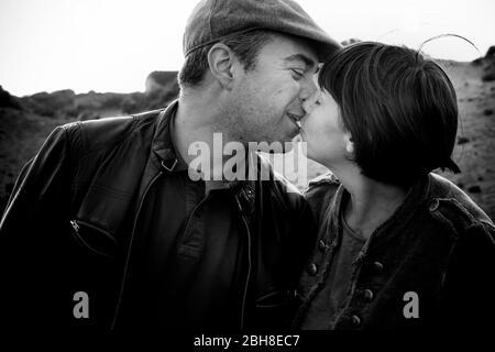 baiser romantique pour couple d'âge moyen éthersexuel caucasien dans les couleurs noir et blanc - amour et vie ensemble concept pour les personnes extérieures - première date ou concept marié - baiser de bonheur Banque D'Images