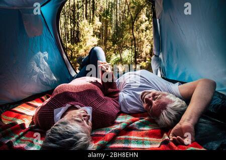 les couples adultes âgés reposent à l'intérieur d'une tente dans un camping sauvage gratuit dans la forêt pour un voyage et un style de vie alternatifs. L'amour pour toujours ensemble concept pour l'homme et la femme prenant les mains et de regarder eachOther - activité de nature extérieure Banque D'Images