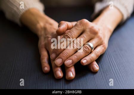 Gros plan sur la femme mûre avec des mains claspées sur la table