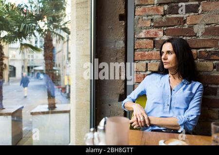 Femme mûre réfléchie regardant par la fenêtre tout en étant assise au café