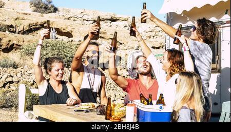 Un concept amusant de succès et d'amitié avec un groupe de jeunes hommes et femmes, tous ensemble toaster avec des bières et de la nourriture assis sur une table de bois rurale avec la nature en arrière-plan
