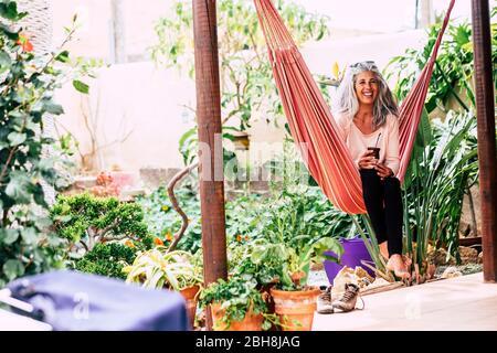 Gai souriant diversité personnes concept avec belle femme adulte à la mode avec des cheveux longs blancs rire s'asseoir sur un hamac à la maison dans le jardin boire un thé