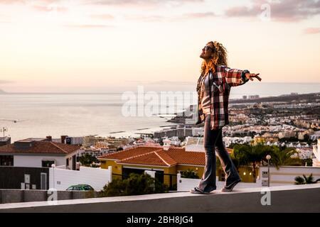 Créativité bonheur liberté et folie concept avec jeune femme blonde maurichement belle marchant en équilibre sur un mur avec la ville et le littoral en arrière-plan - les gens de bonne humeur aiment