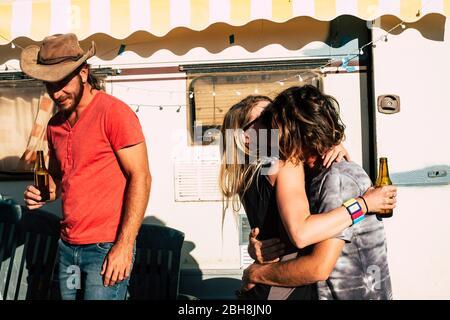 Couple de jeunes gens embrassant avec amour avec un ami marchant dans le dos et souriant - les générations jeunes comme Voyage et profiter de l'aventure en plein air - vieille caravane en arrière-plan Banque D'Images