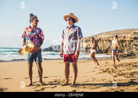 Les groupes d'amis s'amusent ensemble à la plage - hommes debout et filles derrière courir pour jouer - vacances d'été concept de plage - des personnes millénaires avec des vêtements colorés