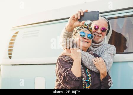 un couple d'adultes heureux et joyeux de 70 ans prend une photo égoïste en dehors d'une fourgonnette bleue avec technologie moderne - le tourisme et le concept touristique pour les gens aiment voyager ensemble dans la relation pour toujours - le bonheur à la retraite
