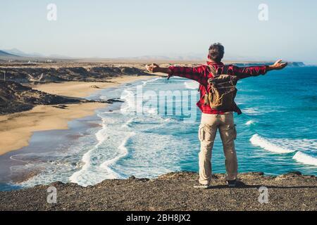 Seul voyageur heureux avec sac à dos les gens qui apprécient la plage de destination se tenant sur une falaise et les bras d'ouverture pour le succès et le concept joyeux - indépendance et beau lieu de nature extérieure Banque D'Images