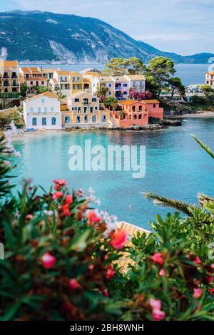 Belles maisons colorées du sud et baie bleue de la mer Méditerranée avec quelques fleurs rouges au premier plan. Village d'Assos à Kefalonia, Grèce. Prise de vue verticale. Banque D'Images