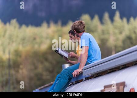 deux personnes assises sur le toit de l'école de bus lisant le guide d'escalade Banque D'Images