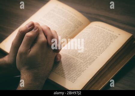 Prière, l'homme se charge d'un livre ouvert Sainte Bible, fond de bureau en bois. Concept de foi, de religion et de spiritualité