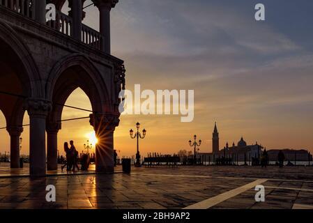 Palais des Doges sur la place Saint Marc avec des amoureux romantiques dans le rétroéclairage au lever du soleil dans l'arrière-plan San Giogio Maggiore et le Bacino di San Marco entre les deux