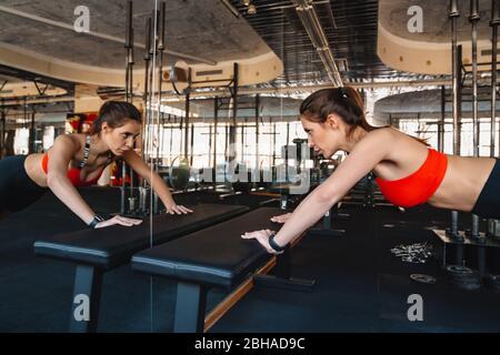 Jeune sportif confiant faisant des poutrements dans la salle de gym Banque D'Images