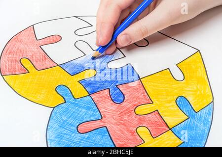 Journée mondiale de sensibilisation à l'autisme. La main des enfants tire le coeur des puzzles multicolores. Concept de soins de santé mentale.