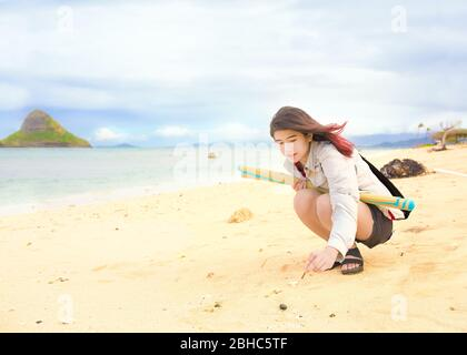 Une jeune fille asiatique d'adolescence biraciale avec des cheveux roses teints se fléchissant pour écrire quelque chose dans le sable sur la plage hawaïenne vide sur Oahu au chapeau de Chinaman, la plage de Kualoa Banque D'Images