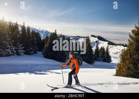 L'homme sur le ski de poudreuse la neige en forêt dans les montagnes près de Almaty, Kazakhstan Banque D'Images