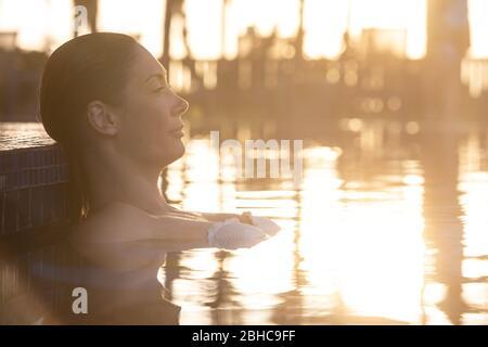 Femme se reposant au coucher du soleil près de la piscine. Lumière intense et chaude. Superbes traits du visage visibles dans le profil. Réflexions de lumières dans l'eau. Vacances d'été Banque D'Images