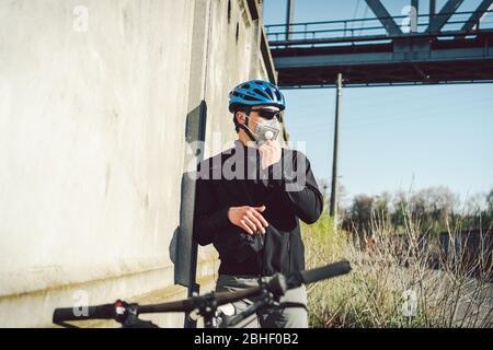 Cycliste en masque de visage en raison du smog dans la ville. Livraison par messagerie de vélo. Homme portant un masque de coronavirus covid 19. Cycliste dans le masque de pollution de