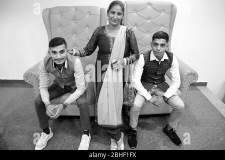 Portrait de famille à la maison sur le canapé. Jeune mère avec ses deux jeunes fils et ils regardent tous la caméra