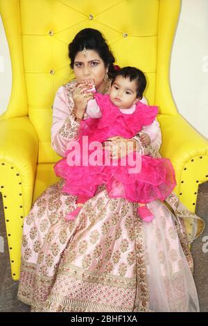 Mère embrassant sa petite fille et les deux assis sur un canapé jaune de luxe portrait de près Banque D'Images
