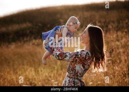 Belle femme lève haut son adorable fille de bébé en plein air et regarde son sourire. Joyeux parent passer du temps à jouer avec sa fille dans le parc à