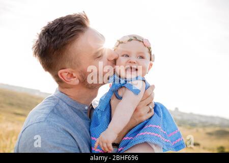 Portrait romantique d'un père heureux tenant sa petite fille en riant dehors. Papa embrasse sa petite fille douce petit enfant tout-petit. Fête des pères heureux