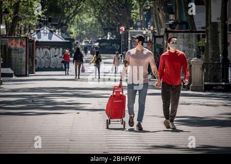 Un couple portant des masques de visage comme mesure préventive marche arrière à la maison après les achats au milieu de Covid-19 pandémique.Barcelone fait face au 42ème jour de confinement et de distanciation sociale. Seuls les établissements autorisés sont ouverts au public. Les rues restent vides sans piétons ni véhicules.