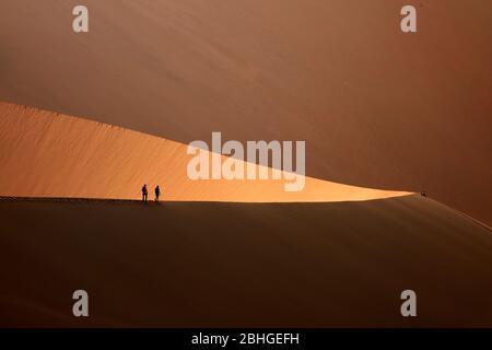 Les gens qui grimpent sur des dunes de sable à côté de Deadvlei, près de Sossusvlei, du parc national du Namib-Naukluft, Namibie, Afrique Banque D'Images