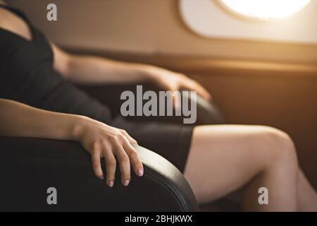 Photo courte d'une femme d'affaires avec peur de vol dans un jet privé. Foyer sélectif de la femme terrifiée assis encombrer les bras de la chaise en privé p
