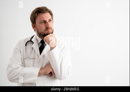 Portrait d'un médecin mâle avec stéthoscope en uniforme médical tenant la main sous son menton, ayant douté poser sur un fond blanc isolé