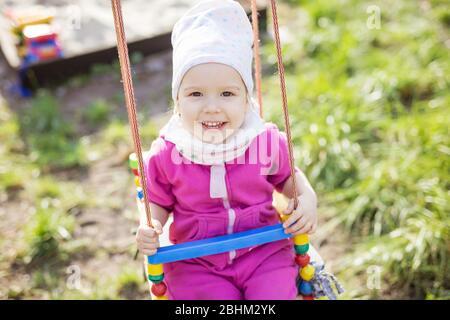 Bonne petite fille sur des balançoires dans le jardin de printemps. Jolie fille regardant l'appareil photo et souriant.