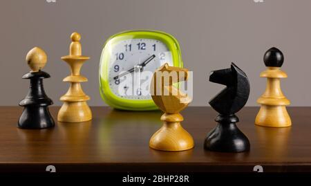 Deux chevaliers se faisant face sur une table en bois, avec un réveil et d'autres pièces d'échecs en arrière-plan