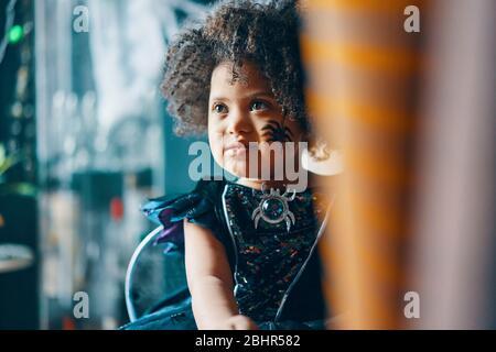 Un enfant aux cheveux fclés foncés dans une robe noire avec son visage peint avec une araignée. Banque D'Images