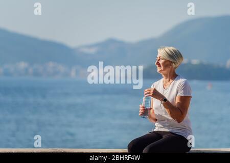 Femme mûre buvant de l'eau après le jogging sur fond de la mer et du ciel bleu