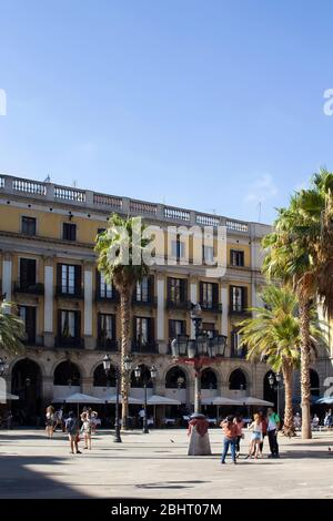 Vue sur les personnes accrochées sur une célèbre place de la ville appelée « Placa Reial », palmiers et bâtiments historiques traditionnels à Barcelone. C'est ensoleillé