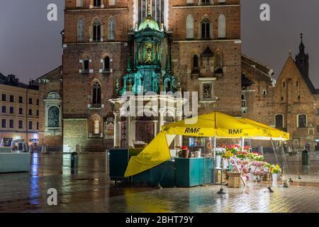 Soirée de pluie sur la place du marché de Cracovie avec kiosque vendant des fleurs Banque D'Images
