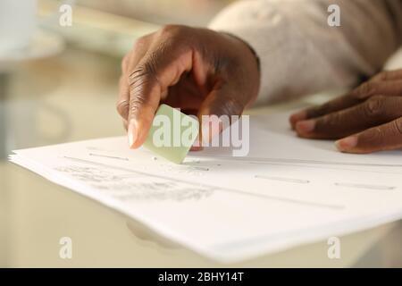 Gros plan sur les mains noires de l'homme gommant le dessin avec du caoutchouc sur un bureau à la maison Banque D'Images