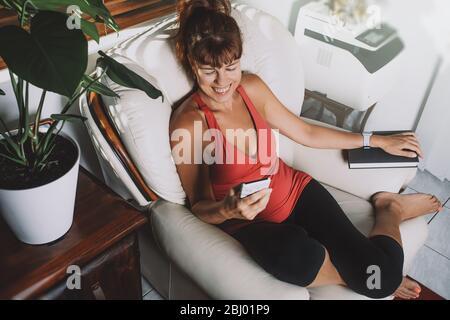 Charmante femme d'âge moyen, en regardant son smartphone et souriante, assise avec un livre assis sur un fauteuil dans un salon.
