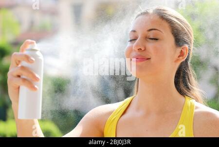 Jeune femme pulvérisant de l'eau thermique sur son visage à l'extérieur. L'eau thermique utilisée pour les soins de la peau, le maquillage fixe, aide à l'irritation de la peau, rougeurs et piqûres d'insectes.