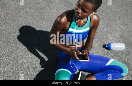 Vue de dessus d'une femme avec son téléphone mobile assis sur la route après une course matinale et regardant loin. Installer une femme sur la route en prenant une pause après un travail en plein air