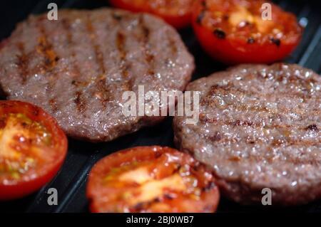 Hamburgers et tomates coupées grillés sur une poêle gril non-adhésive - Banque D'Images