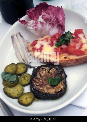 Plaque antipastis d'anchois marinés, aubergines grillées, salade de Raccchio, courgettes grillées et bruchetta garnie de tomates et de fromage au repos Banque D'Images