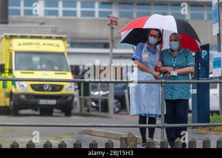 Southend University Hospital, Southend on Sea, Essex, Royaume-Uni. 28 avril 2020. Le jour commémoratif international des travailleurs a eu lieu une minute de silence à 11 heures pour se souvenir des soins de santé et des soins sociaux et des autres travailleurs clés morts à la suite de la pandémie de Coronavirus COVID-19. Des paires de chaussures ont été placées sur le green à l'extérieur de l'hôpital de Southend comme un rappel visuel des plus de cent employés de première ligne qui ont perdu la vie, y compris un certain nombre de personnes de Southend Banque D'Images