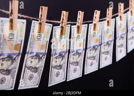 Concept de blanchiment d'argent - cent factures pendent sur un cordon contre fond gris