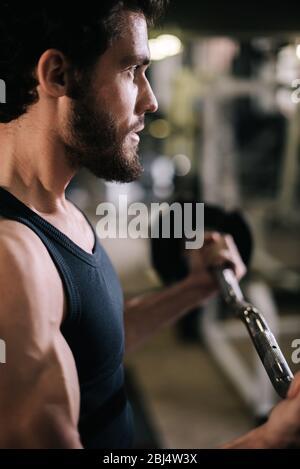 Gros plan sur le visage de beau homme barbu avec corps musclé qui travaille avec barbelette. Banque D'Images
