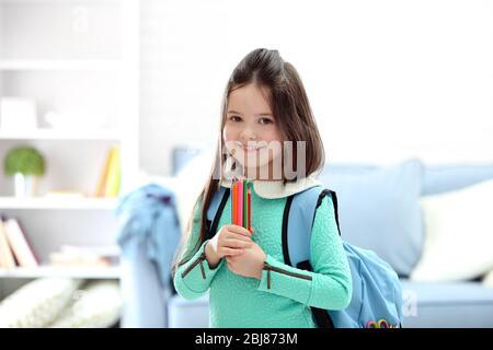 Petite fille avec sac à dos bleu tenant des crayons de couleur dans le salon Banque D'Images