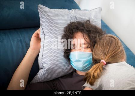 Le père caucasien porte un masque facial pour éviter la contagion en dormant avec une petite fille d'enfant pendant le verrouillage de la pandémie de covid-19. Papa et fille endormie. Banque D'Images