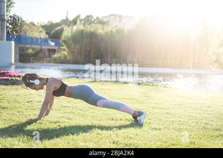 femme de sport faisant des exercices sur gazon et s'étirant sur l'herbe en plein air dans un parc écoutant de la musique Banque D'Images