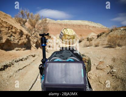 Touriste avec sac à dos et panneau solaire à canyon sur surreal montagnes rouges sur fond de ciel bleu dans le désert Banque D'Images