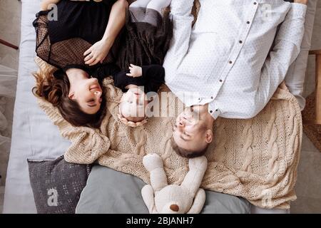 Belle jeune famille posée ensemble sur le lit à la maison, maman, papa et fille de bébé, vue de dessus. Fête des mères, des pères, des bébés. Famille passer du temps Banque D'Images